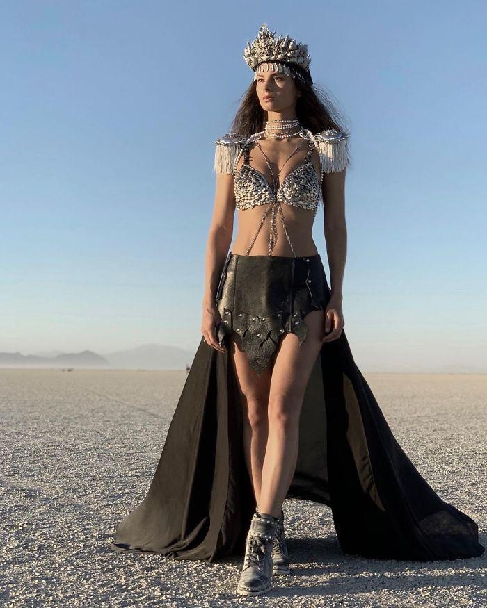 Kobieta na pustyni w czarnej sukni z koroną na głowie