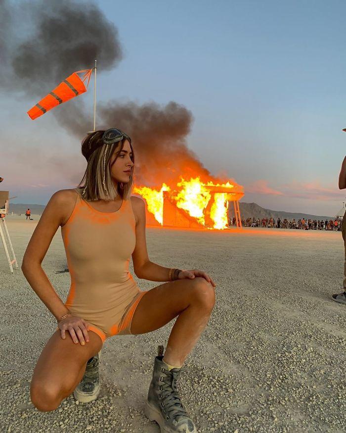 Kobieta w beżowym kostiumie na tle palącego się budynku na pustyni