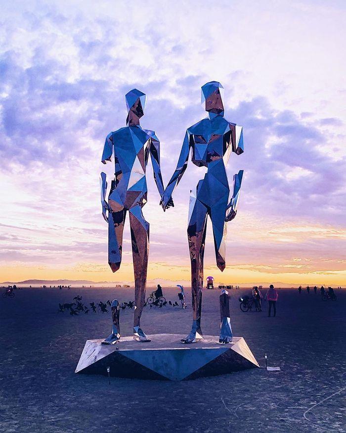 Instalacja na pustyni, dwie postacie zrobione z metalu na tle pomarańczowo-niebieskiego nieba