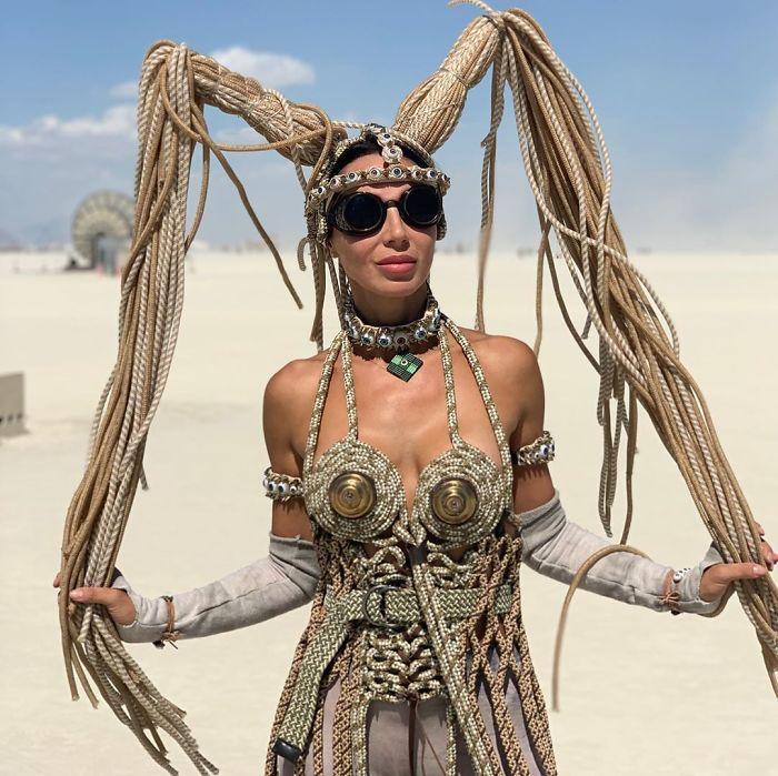 Kobieta w beżowym kostiumie na pustyni, ubrana w czarne okulary