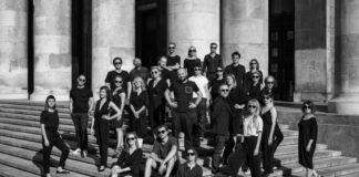 Czarno-białe zdjęcie ukazujące grupę osób zebranych na schodach. W tle widać kamienne filary.