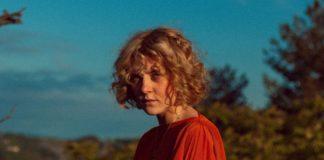 Dziewczyna w krótkich włosach, ubrana w czerwoną bluzkę a tle lasu i błękitnego nieba