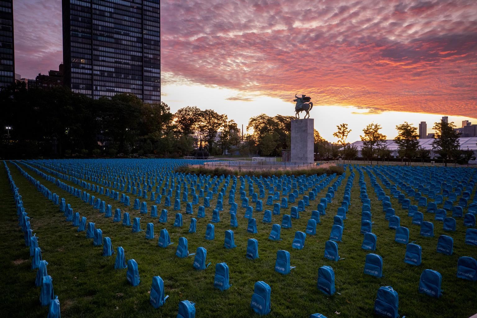Błękitne plecaki z logo UNICEF, ustawione rzędami na polanie. W tle zachodzące słońce.