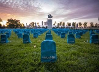 Błękitne plecaki z logo UNICEF, ustawione rzędami na polanie.