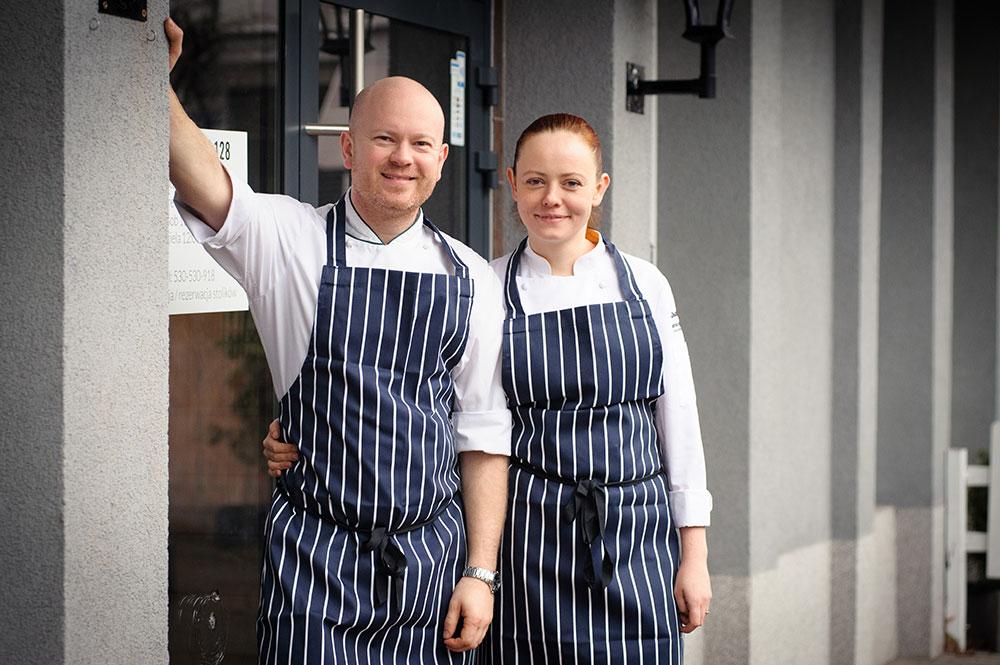 Kobieta i mężczyzna w fartuchach kuchennych, stojący przed restauracją