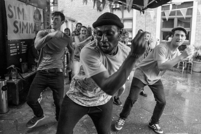 Czarno-białe zdjęcie przedstawiające trójkę tańćzących ludzi