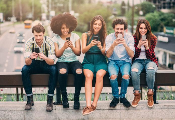 Grupa przyjaciół siedząca na ławce ze smartfonami w dłoniach
