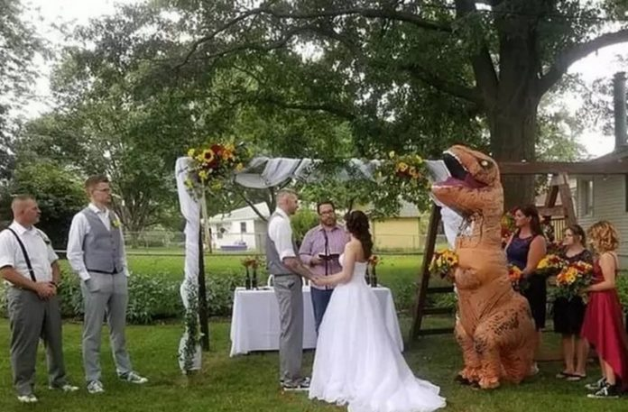Para biorąca ślub i dziewczyna w stroju dinozaura
