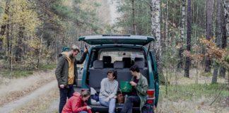 Grupa przyjaciół siedząca przy samochodzie