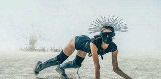 kobieta w czarnym stroju z kolcami na głowie oraz w masce na pustyni