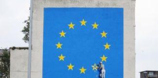 Flaga Unii Europejskiej i mężczyzna odłupiający jedną gwiazdę