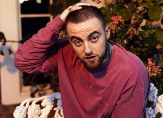 Mężczyzna w czerwonej bluzce trzyma się za głowę.
