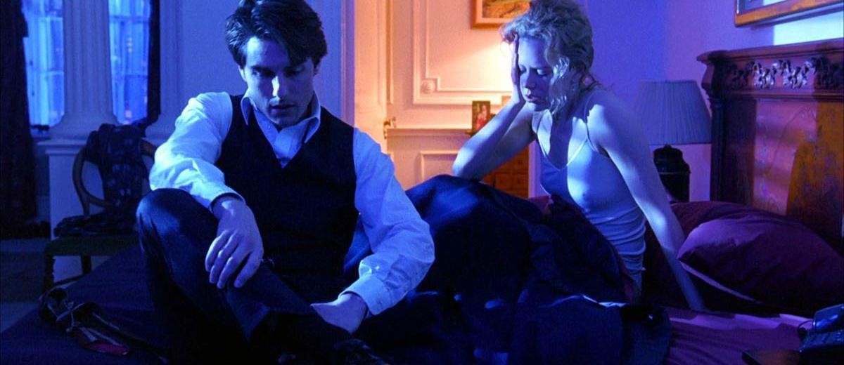 dwoje ludzi siedzących na łóżku w niebieskim świetle