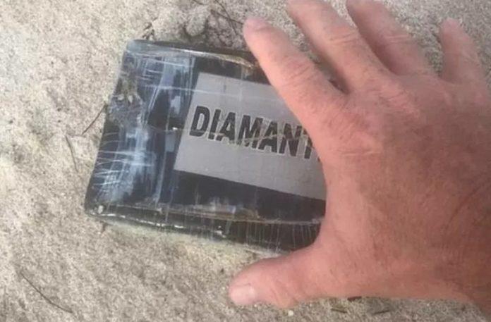 Dłoń podnosząca cegłe owiniętą folią