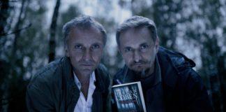 Dwóch mężczyzn w lesie trzrymajacych ksiazke w dłoni