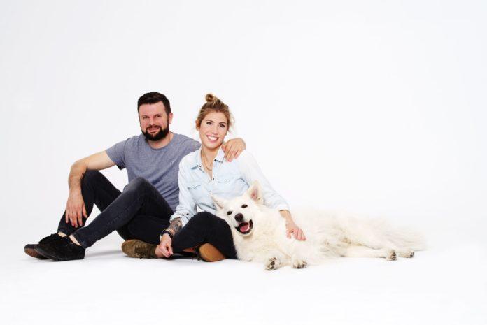 Kobieta i mężczyzna siedzący na ziemi z psem