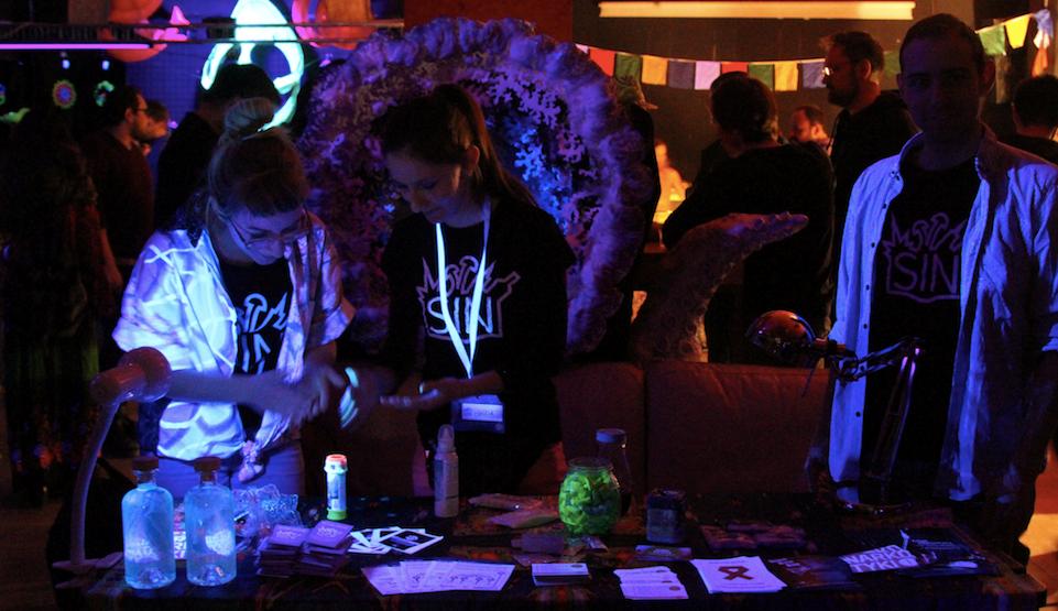 Kilka osób stojących przy stole, w ciemnej przestrzeni, na imprezie, oświetlonej lampką biurkową i kilkoma światłami w tle.