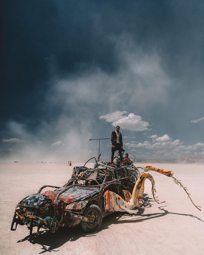 Instalacja przypominająca samochód, na niej stojący człowiek, pustynia