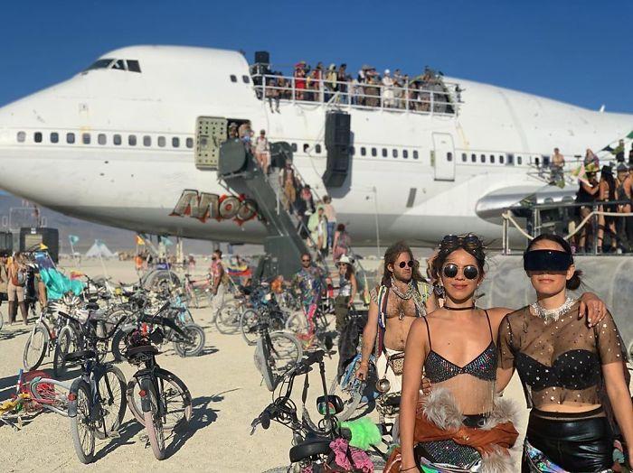 Biały samolot na pustyni, ludzie stojący na nim oraz przechodzący obok, rowery
