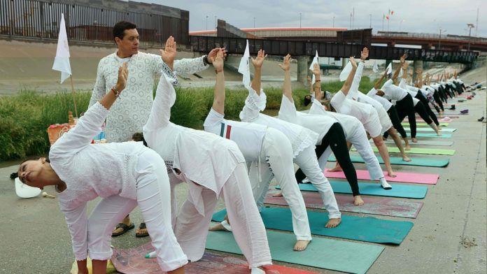 Ludzie ubrani na biało praktykują jogę na dworze. W tle widać mur