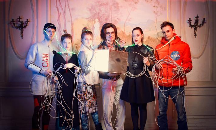 Sześć osób ubranych w kolorowe stroje. Trzymają kable i lampę