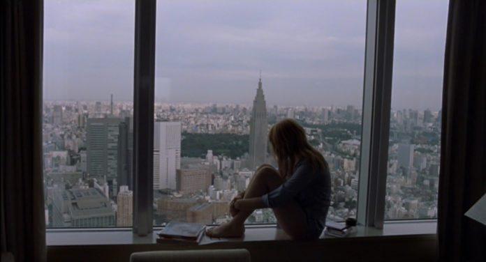 Kobieta siedząca na parapecie okna (Scarlett Johanson) wpatrzona w panoramę Tokyo