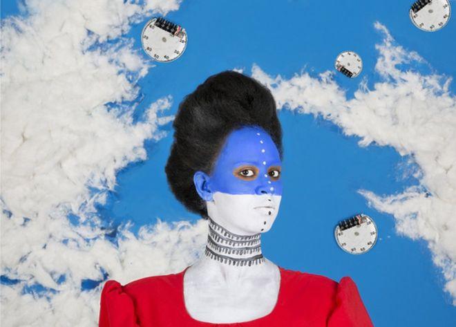 Zdjęcie przedstawia kobietę z półprofilu o pomalowanej na biało błękitnej buzi. W tle widać makietę, która ma przypominać błękitne niebo i chmury