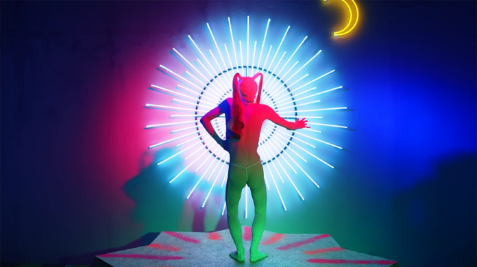 Kadr z teledysku Aishy Devi - Mazda przedstawiający postać artystki stojącej tyłem na tle emanującej energią aureolidowej elektroniki