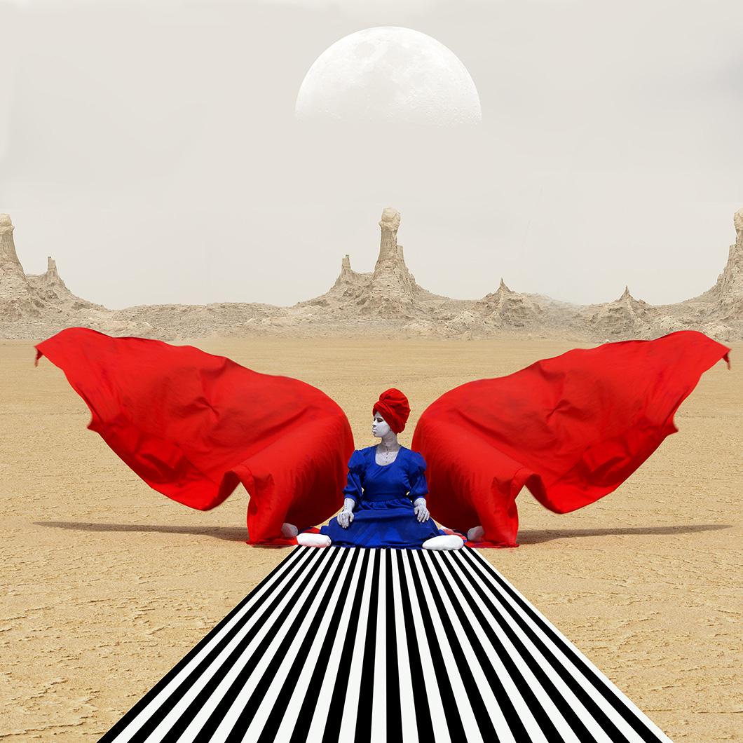 Zdjęcie przedstawia kobietę ubraną w niebieską suknie i czerwony turnab siedzącą przed czarno-białym dywanem. Obraz jest symetryczny po obu jej stronach widać czerwony materiał przypominający skrzydła. W tle widnieje pustynia i wielki półksiężyc