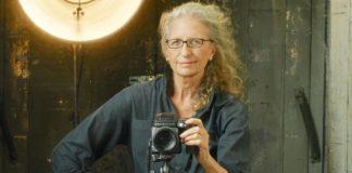 Kobieta z rozpuszczonymi włosami trzymająca w dłoni aparat