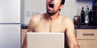 Półnagi mężczyzna oglądający coś na laptopie