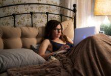 Kobieta leżąca z laptopem w łóżku