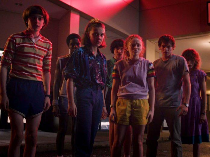 Grupa nastolatków stojąca przed budynkiem w czerwonym świetle