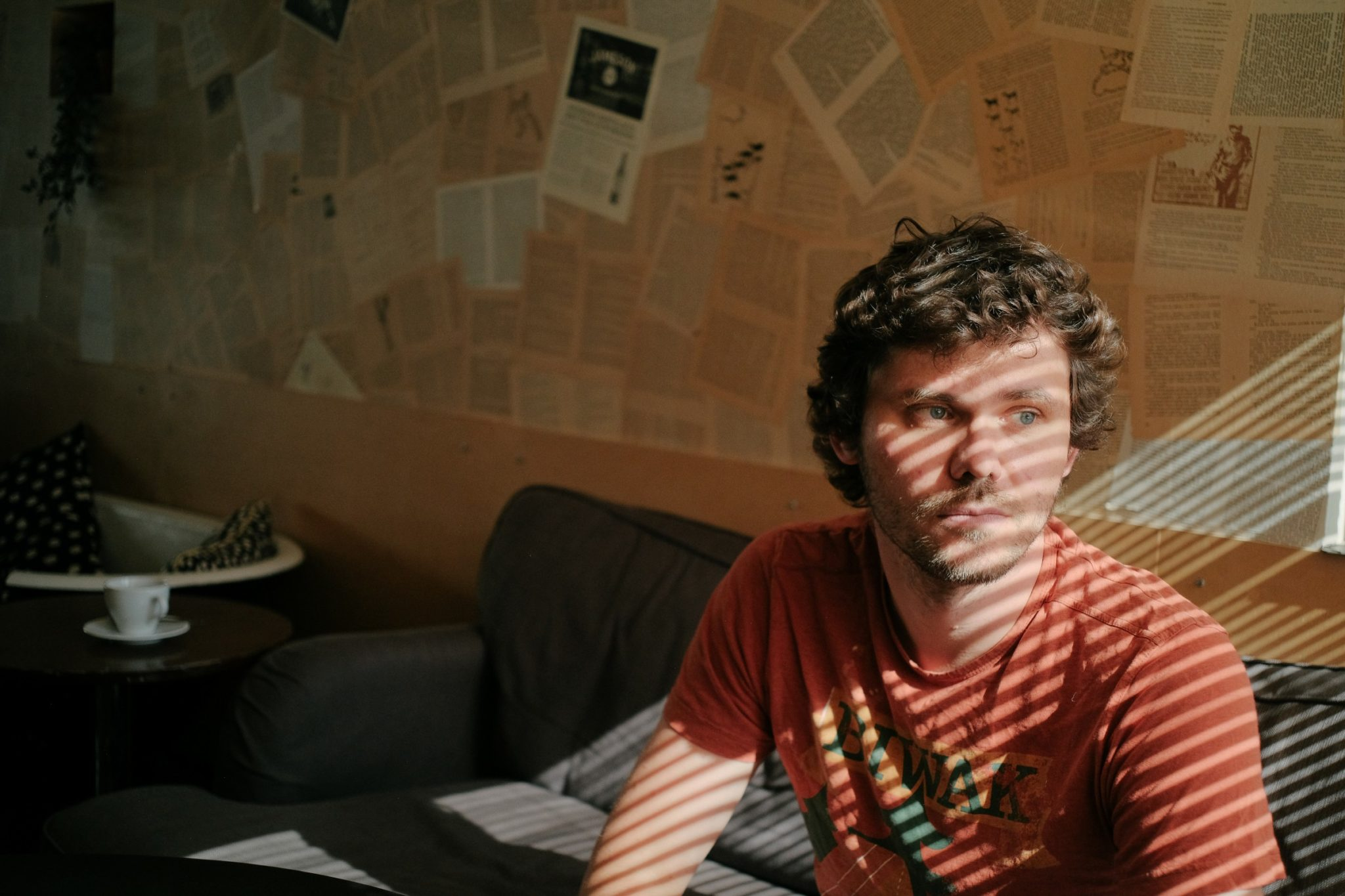 Mężczyzna siedzący w kawiarni ze światłem padającym mu na twarz