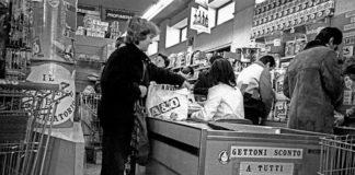 Czarno-białe zdjęcie przedstawiające kobietę przy kasie sklepowej