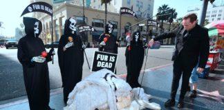 Cztery osoby przebrane za kostychy i futra leżące na ziemi