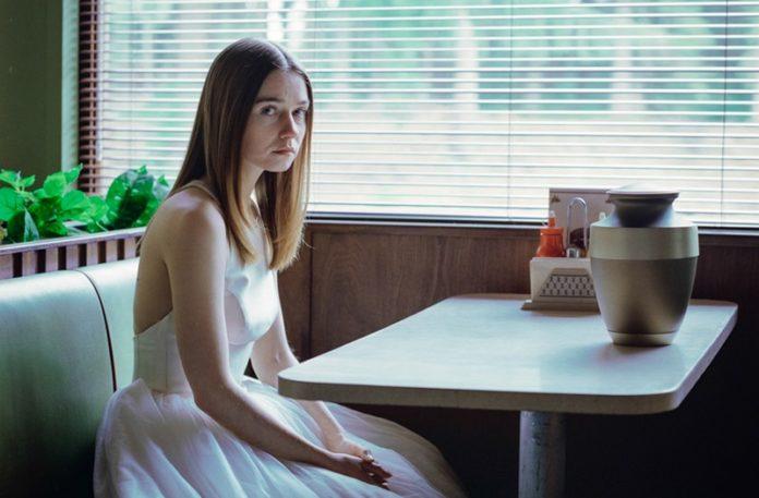 Dziewczyna w białej sukience siedząca w restauracji