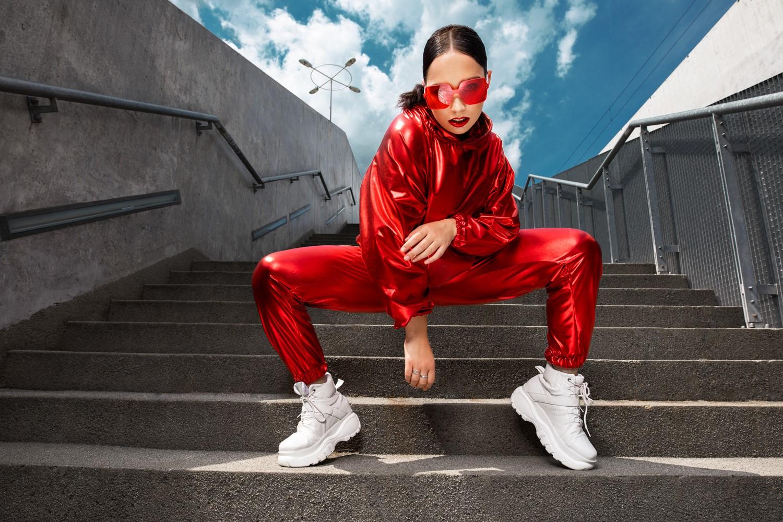 Dziewczyna w czerownych okularach, czerwonym kostiumie i białych butach na schodach