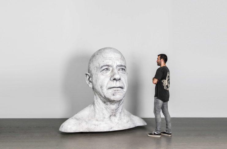 Mężczyzna stojący obok popiersia mężcyzny