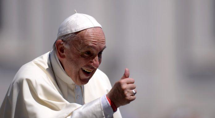 Zdjęcie przedstawia papieża franciszka, uśmiechniętego, pokazującego