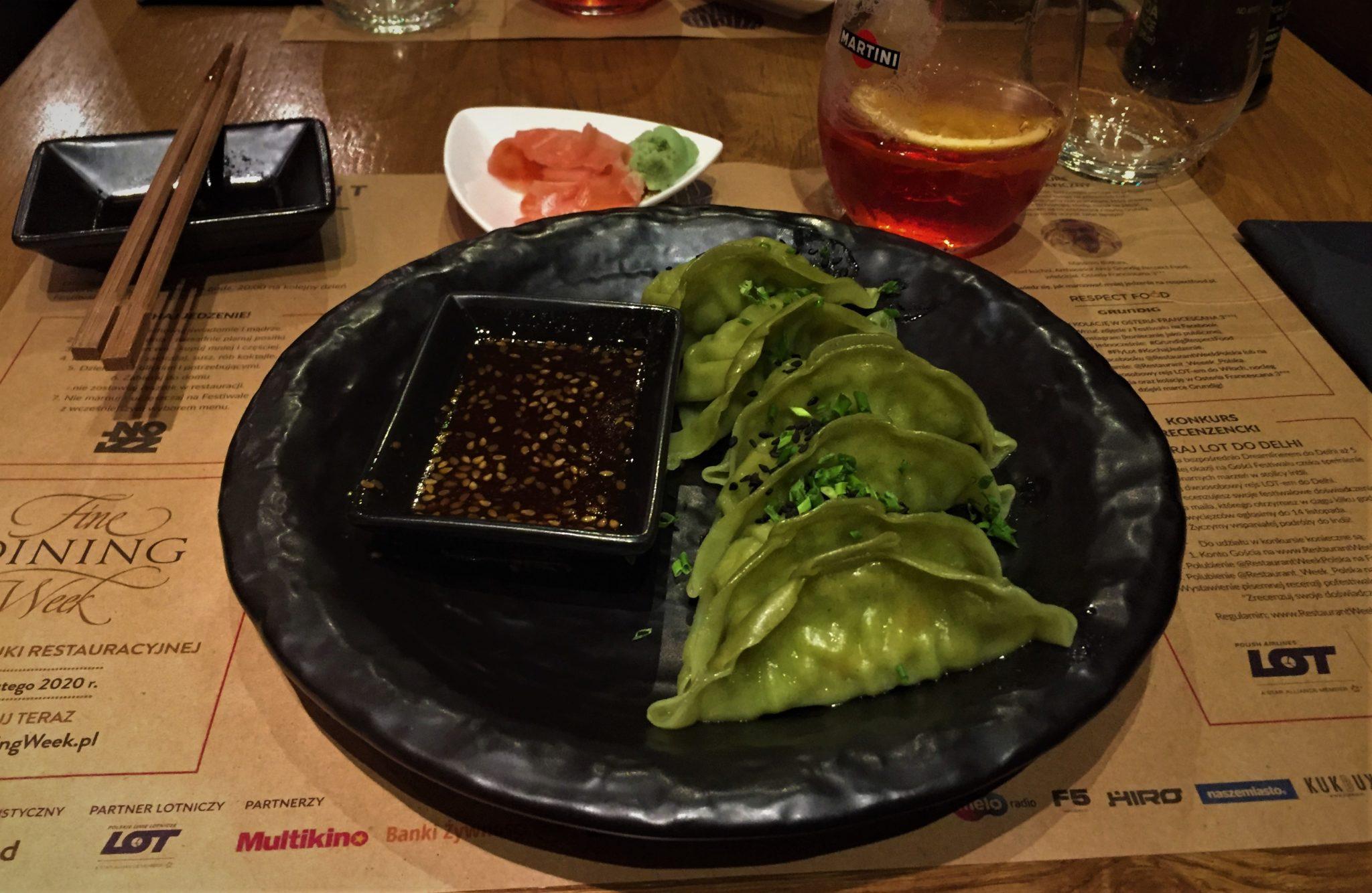 Zielone, japońskie pierożki, z ciemnym sosem sezamowym, na czarnym talerzu, w tle drink martini