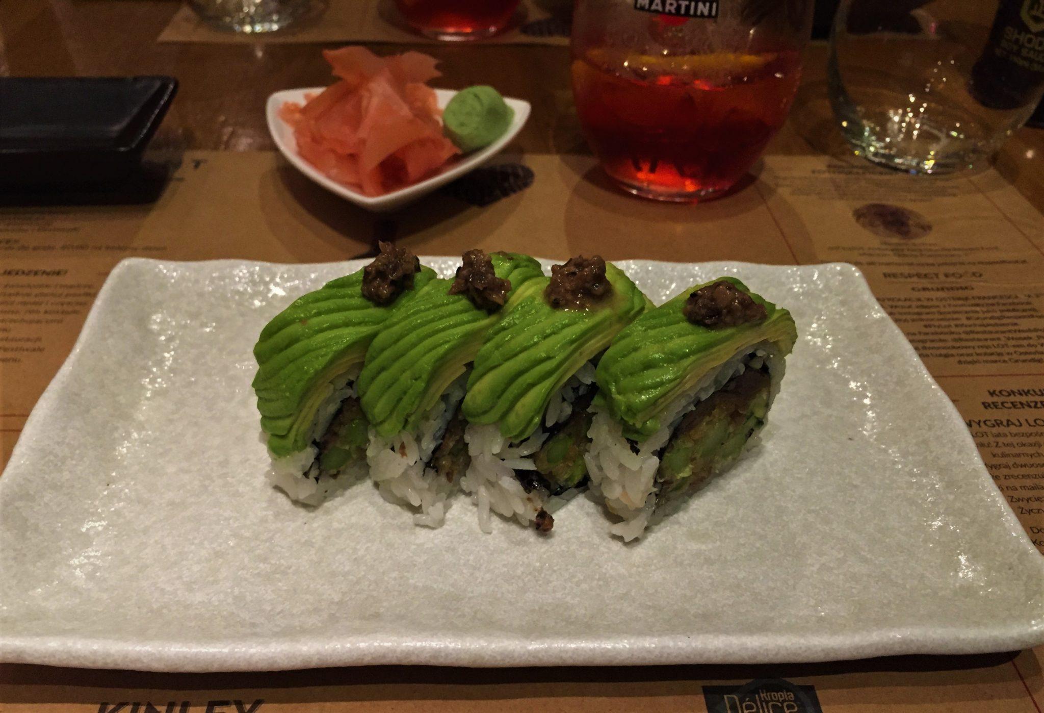 Sushi na białym talerzu, w tle drink martini