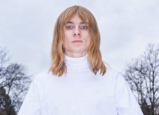 Mężczyzna ubrany na biało z długimi blond włosami