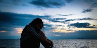 Dziewczyna siedząca na drewnianym pomoście nad jeziorem