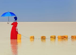 Zdjęcie przedstawia kobietę ubraną w czerwoną suknię trzymającą błękitny parasol na tle błękitnego nieba. Idzie ona przez jezioro, ciągnąc za sobą żółte kanistry na wodę