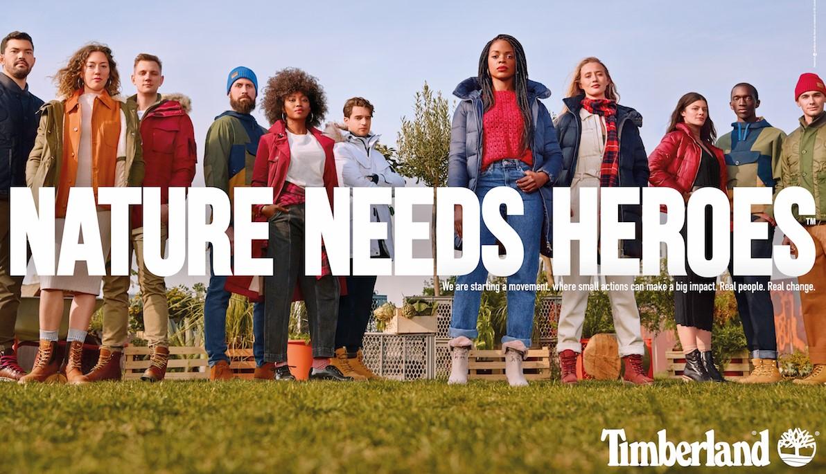 Ludzie stojący na trawniku. Napis na całość ilustracji. W języku angielskim: Natura potrzebuje bohaterów
