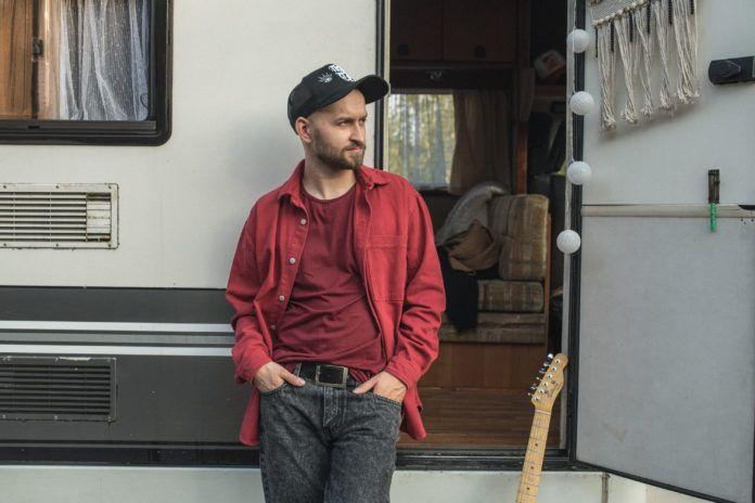Mężczyzna w czerwonej koszuli oparty o przyczepę kempingową