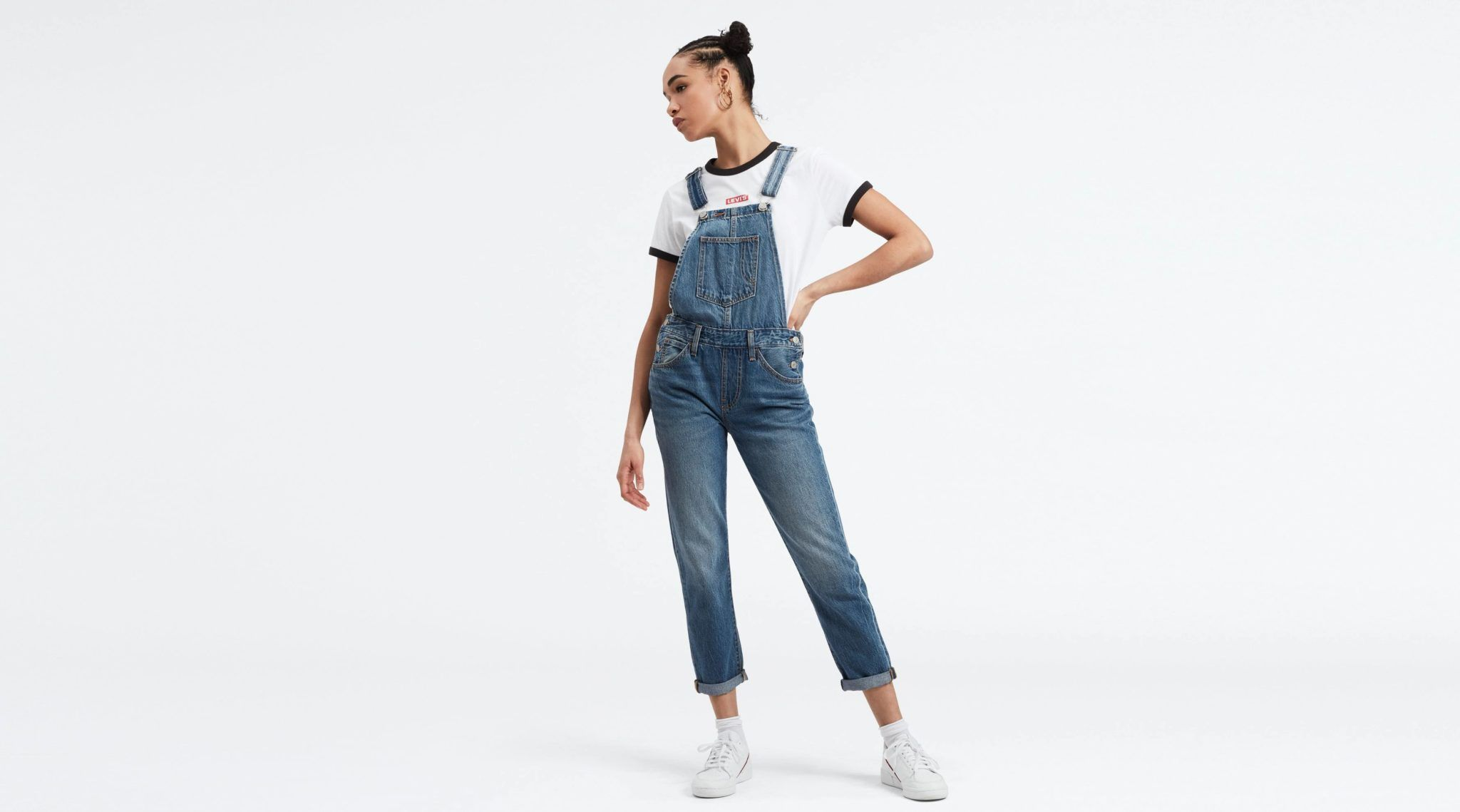 Młoda kobieta ubrana w jeansowe ogrodniczki, stojąca na białym tle