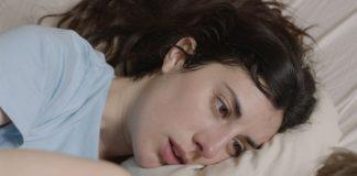 Kobieta leząca na łóżku obok mężczyzny