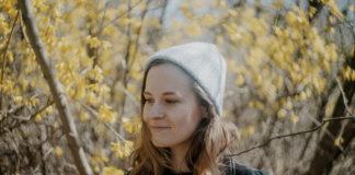 Dziewczyna w szarej czapce na tle jesiennych liści
